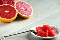 Slices of grapefruit on a plate, a spoon and a grapefruit Stock Photo