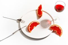 Slices of grapefruit on a white plate. Minimalistic concept. Top view royalty free stock image