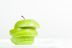 Slices of green apple in a  plate. Slices of green apple in a white plate Stock Photo