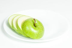 Slices of green apple in a  plate. Slices of green apple in a white plate Stock Photos