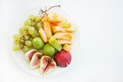 Slices of green figs of melon and grapes. Slices of green figs of melon and grapes royalty free stock photography