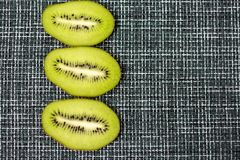 Slices of green kiwi on a grey checkered cloth. Slices of juicy green kiwi on a grey checkered napkin with a copy of space Stock Images