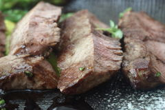 Slices of Grilled Beef. On a stone plate Royalty Free Stock Photos