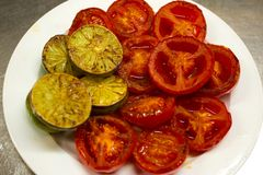 Slices of grilled tomatoes and lemons on a plate. Some slices of grilled tomatoes and lemons on a white plate stock photo