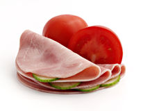 Slices of ham with cucumber and tomato. Isolated on the white background Stock Photo