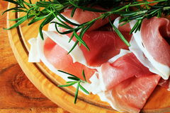Slices of ham on a cutting board. Slices of ham and rosemary on a cutting board Stock Photo