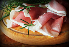 Slices of ham on a cutting board. Slices of ham and rosemary on a cutting board Stock Photography