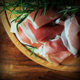 Slices of ham on a cutting board. Slices of ham and rosemary on a cutting board Royalty Free Stock Images