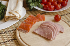 Slices of ham and salmon on a board Royalty Free Stock Photos