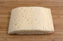 Slices of Havarti cheese on a cutting board Royalty Free Stock Image