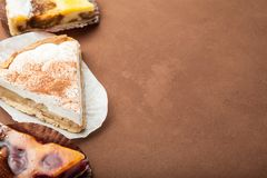 Slices of a homemade pie on a brown background, empty space for text royalty free stock image