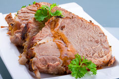 Slices of homemade roast pork close up. Slices of homemade roast pork on the plate Royalty Free Stock Photography