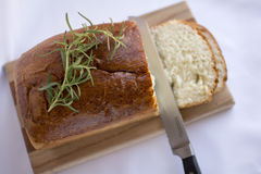 Slices of homemade white bread loaf on wood cutting board. Delicious slices of  homemade white bread loaf on wood cutting board with rosemary and cutting knife Royalty Free Stock Photos