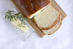 Slices of homemade white bread on wood cutting board. Delicious slices of  homemade white bread loaf on wood cutting board with butter and rosemary on white Royalty Free Stock Image