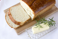 Slices of homemade white bread on wood cutting board. Delicious slices of  homemade white bread loaf on wood cutting board with butter and rosemary on white Stock Photo