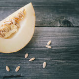 Slices of honeydew melon on gray wooden table Royalty Free Stock Photo