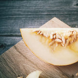 Slices of honeydew melon on gray wooden table Stock Photography