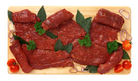 Slices of horse meat. On wooden board Stock Photography
