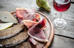Slices of italian ham on the wooden board Stock Images
