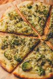 Slices of italian pizza with broccoli and cheese. Slices of italian pizza with broccoli, pesto sauce and cheese on baking paper. High angle view royalty free stock image