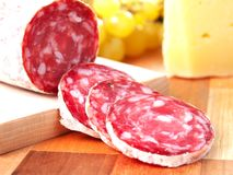 Slices of italian salame on chopping board Stock Photo