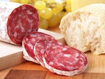 Slices of italian salame on chopping board Royalty Free Stock Image