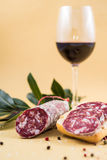 Slices of italian salami on bread and some spices and wine. Slices of italian salami on bread and some spices and red wine in glass Royalty Free Stock Image