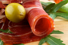 Slices of jamon and olives. Close up on wooden background Stock Photos