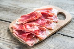 Slices of jamon on the wooden board Stock Photo