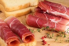 Slices of jamon on a wooden table with fresh herbs. Slices of jamon on a wooden table with herbs and bread Stock Photo