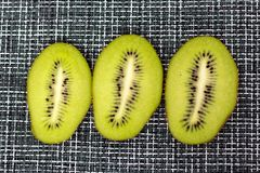 Slices of green kiwi on a grey checkered cloth. Slices of juicy green kiwifruit on a grey checkered cloth Royalty Free Stock Images