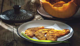 Slices of juicy orange pumpkin with spices, fried on the grill pan Royalty Free Stock Photography