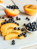 Slices of juicy peaches and blueberries on a white board Stock Photos