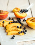 Slices of juicy peaches and blueberries on a white board Royalty Free Stock Photos