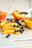 Slices of juicy peaches and blueberries on a white board Stock Photography