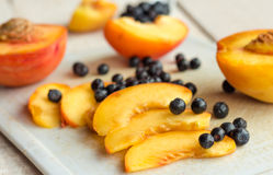Slices of juicy peaches and blueberries on a white board Stock Image