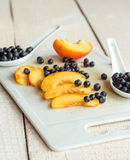 Slices of juicy peaches and blueberries on a white board Royalty Free Stock Photo