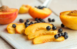 Slices of juicy peaches and blueberries on a white board Royalty Free Stock Image