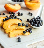 Slices of juicy, sweet peaches and blueberries on white backgrou Royalty Free Stock Image