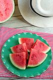 Slices of juicy watermelon on a green plate with a hat. Slices of watermelon on a green plate on wooden background with a hat Stock Photos