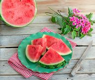 Slices of juicy watermelon on a green plate. Slices of watermelon on a green plate on wooden background Stock Image