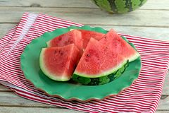 Slices of juicy watermelon on a green plate. Slices of watermelon on a green plate on wooden background Royalty Free Stock Photo