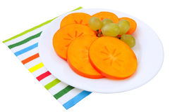 Slices of kai or persimmon fruit and grapes Stock Photos