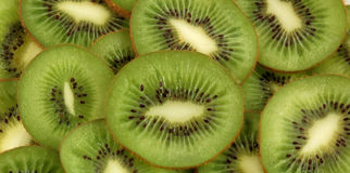 Slices kiwi. Green background slices of kiwi Royalty Free Stock Photo