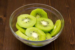Slices of kiwi fruit on bowl over wood Royalty Free Stock Photos