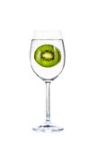 Slices of kiwi fruit and bubble in glass on white background Royalty Free Stock Images