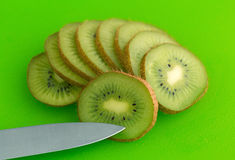 Slices of kiwi fruit on a green cutting board Stock Images