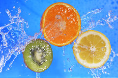 Slices of kiwi,  orange and  lemon. In  water with bubbles Royalty Free Stock Image