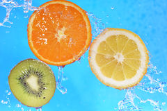 Slices of kiwi,  orange and  lemon. In  water with bubbles Stock Photos