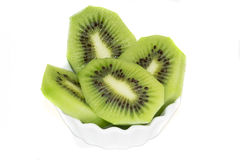 Slices of kiwi in a saucer on a white background  Stock Images